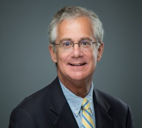 Middle aged man with gray hair and glasses is smiling