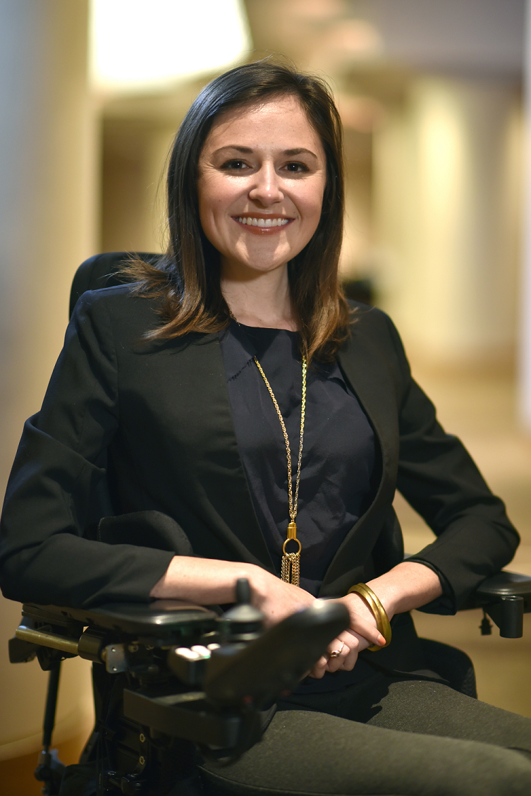 Young woman in her thirties with shoulder length brown hair, who is a wheelchair user, smiles at the camera