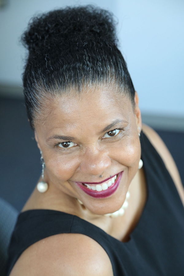 Middle aged African American woman with updo smiles at the camera