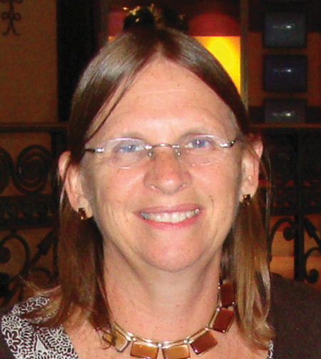 Middle aged woman with shoulder length brown hair and glasses smiles at camera