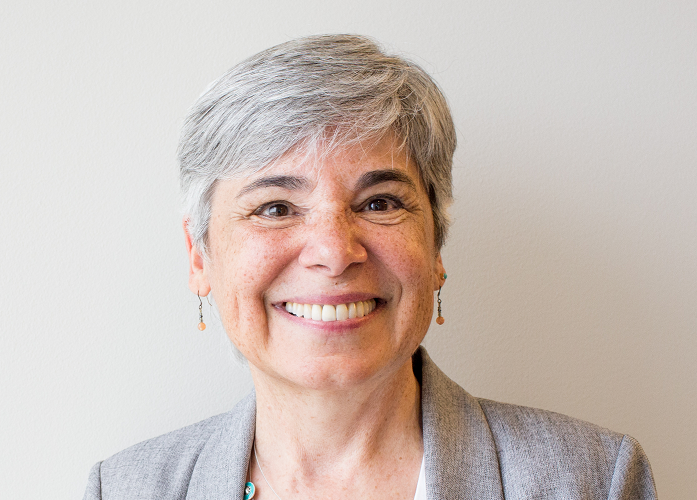 Middle aged woman with short gray hair smiles at camera
