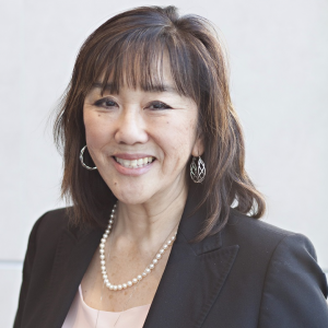 Middle aged Asian women with medium length dark hair smiles at camera
