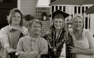 Family - son, father, daughter wearing graduation cap and gown, mother smiling