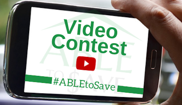 "Hand holding cellphone with ""Video Contest - #ABLEtoSave"" on screen."