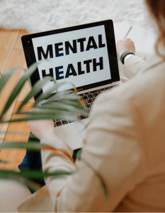 An open laptop with words Mental Health displayed on the screen.